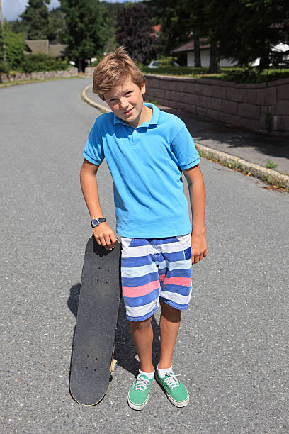 Cool boy leaning on his skateboard, Norway stock photo