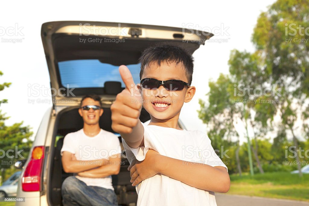 cool boy thumb up and father across arms with car stock photo