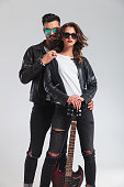 cool couple in leather jackets standing embraced and holding electric guitar on grey studio background