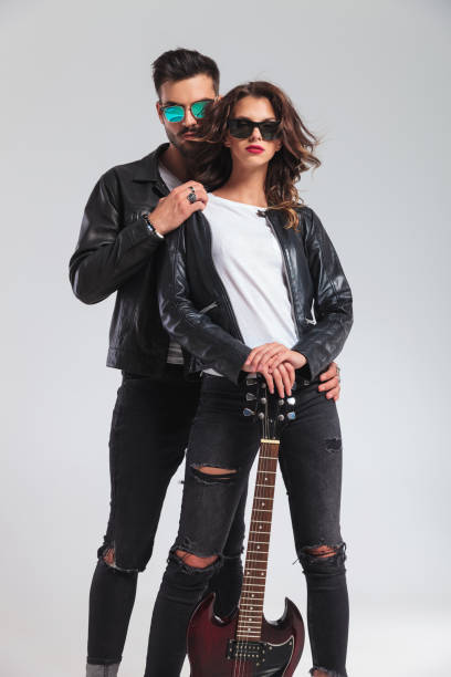 cool couple in leather jackets standing embraced holding electric guitar - punk music stock photos and pictures
