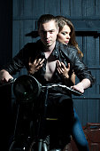 Sexy cool young couple sitting on motorcycle in garage on wooden wall background, vertical picture