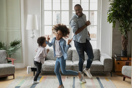 Cool daddy entertaining two children at home. Funny black dad or babysitter and excited active kids dancing, running rounds in living room, laughing, having fun, going crazy. Family activity concept