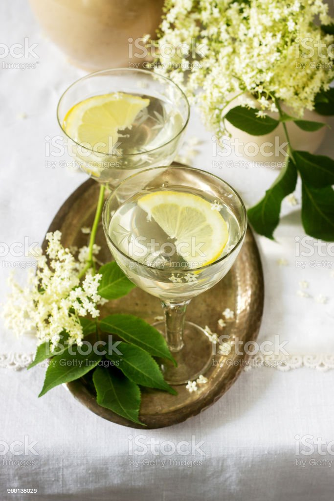 A cool drink with lemon and elderflower syrup in glasses on a metal tray. Rustic style. - Foto stock royalty-free di Agrume