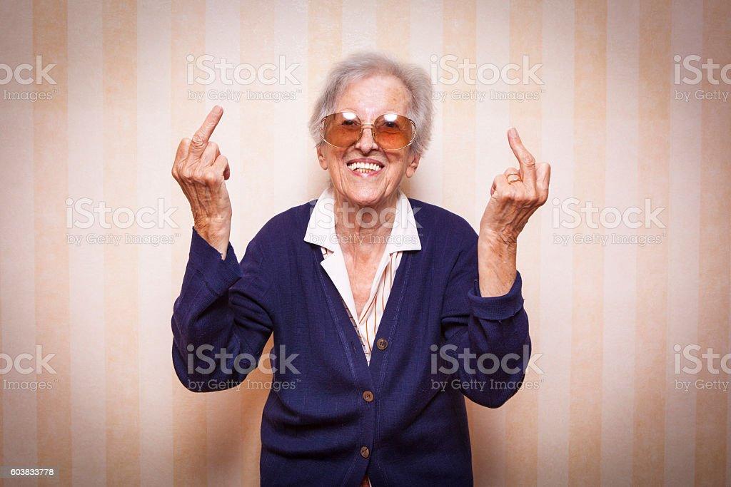 cool elder lady making middle finger sign stock photo