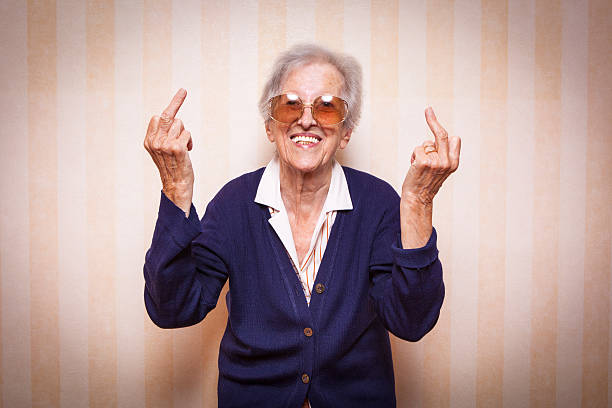 cool elder lady making middle finger sign - swearing stockfoto's en -beelden