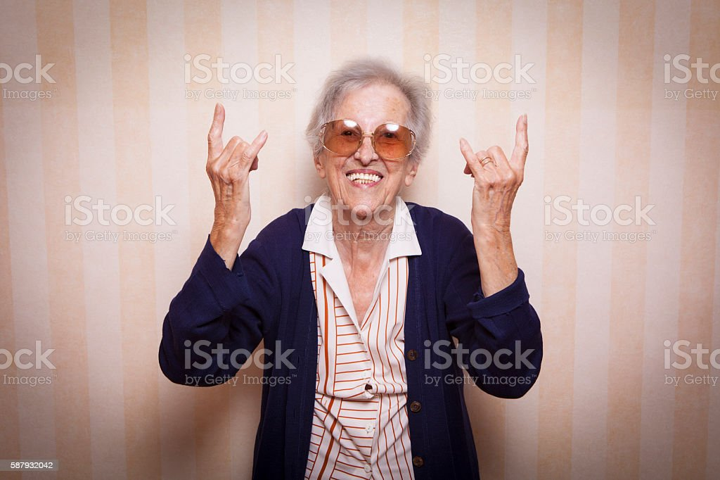 cool elder lady making rock on sign