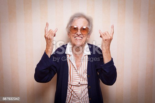 istock cool elder lady making rock on sign 587932042