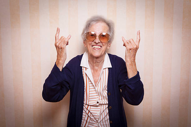 cool elder lady making rock on sign - foto stock