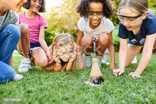 Shot of group of little girls wearing protective glasses doing a soda fountain experiment in garden