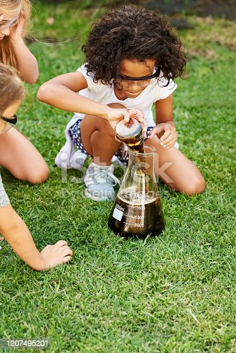 Shot of little girls experimenting in garden, with a girl adding cola in a big glass flask