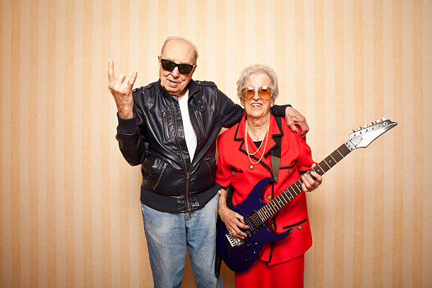 cool fashion elder couple with electric guitar stock photo