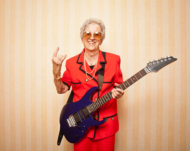cool fashion elder lady with electric guitar stock photo