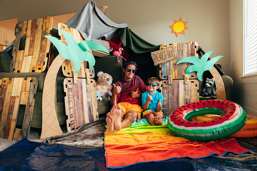 A young boy and his dad are ready to go to the beach they have made for themselves at home. The coronavirus quarantine has forced them from vacation mode to staycation mode. They are staying positive and making the best of the situation.