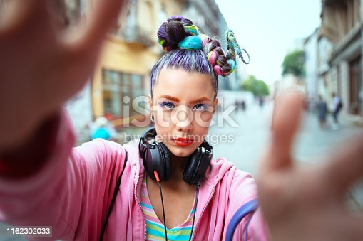 Cool funky young girl with headphones and crazy hair enjoy power of music taking selfie on street - hipster woman with trendy avant-garde look feeling awesome - Music fan concept with carefree teen having fun