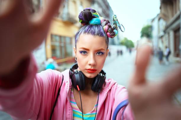 coole funky jong meisje met koptelefoon en gek haar geniet van de kracht van muziek het nemen van selfie op straat-hipster vrouw met trendy avant-garde look awesome-muziek fan concept met zorgeloze tiener met plezier - street style stockfoto's en -beelden