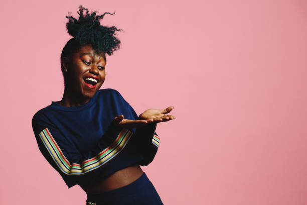 cool girl in a blue sweatshirt laughing and looking at her hands, isolated on pink studio background - carlos david stock pictures, royalty-free photos & images