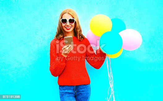 istock Cool girl is using smartphone with an air balloons on a blue background 975191398