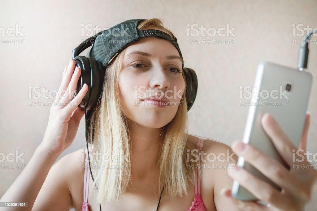 Garota legal escuta música em fones de ouvido sobre fundo branco. Chat de vídeo online. Comunicação. Tirando fotos de si mesmos, tomando selfies. para assistir a um filme em um smartphone. audiobook. - foto de acervo
