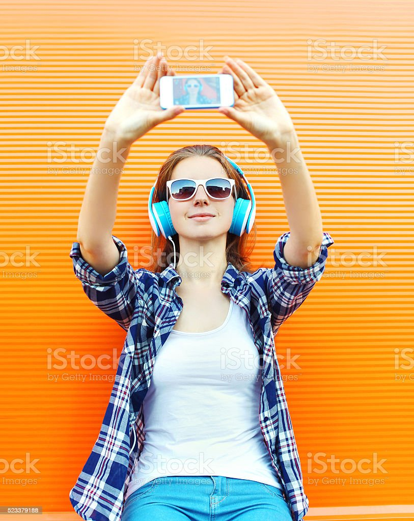 Cool girl makes self portrait on smartphone and listens music stock photo