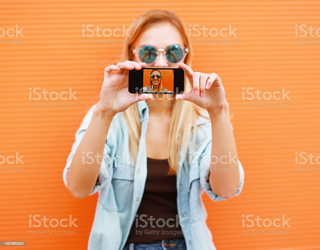 cool girl makes self-portrait on the smartphone stock photo