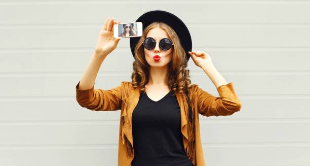 Cool girl model taking photo picture self-portrait on smartphone wearing retro elegant hat, sunglasses, brown jacket and handbag with curly hair over city grey background stock photo