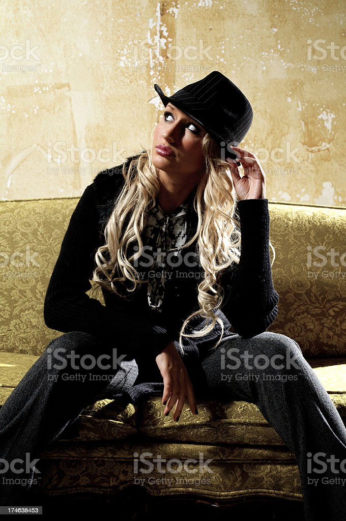 cool girl sitting on a old couch and looking away royalty-free stock photo