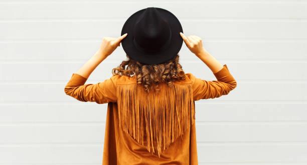 cooles mädchen blick von hinten trägt einen schwarzen hut, sonnenbrille und jacke über urbane grauen hintergrund - bedruckte leggings stock-fotos und bilder