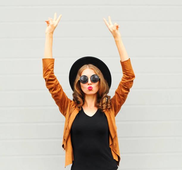 cooles mädchen trägt einen schwarzen hut, sonnenbrille und jacke erhebt hände über urbane grauen hintergrund - bedruckte leggings stock-fotos und bilder