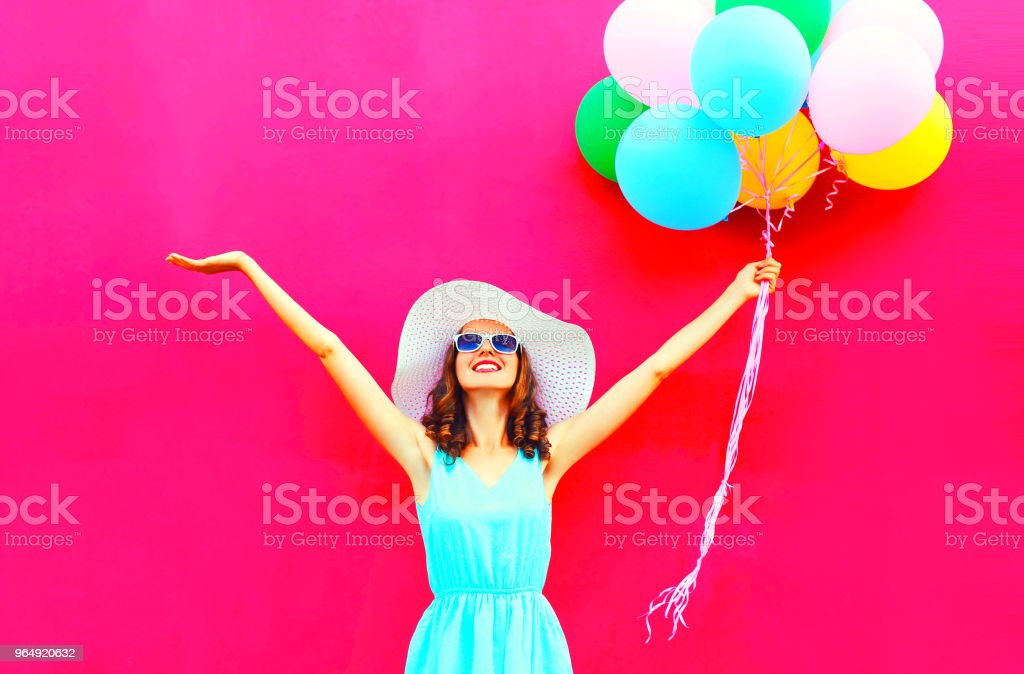 Cool girl with an air colorful balloons is having fun in summer over pink background stock photo