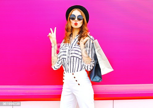 istock Cool girl with shopping bags wearing a black hat white pants over colorful pink background 961999238