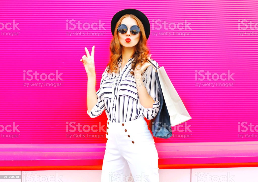 Cool girl with shopping bags wearing a black hat white pants over colorful pink background stock photo