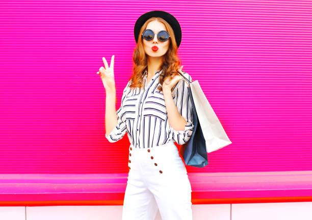 Coole Mädchen mit Einkaufstaschen tragen einen schwarzen Hut weiße Hosen über bunte rosa Hintergrund – Foto