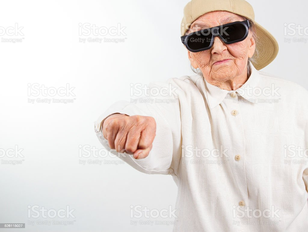cool grandma kicks with her fist stock photo