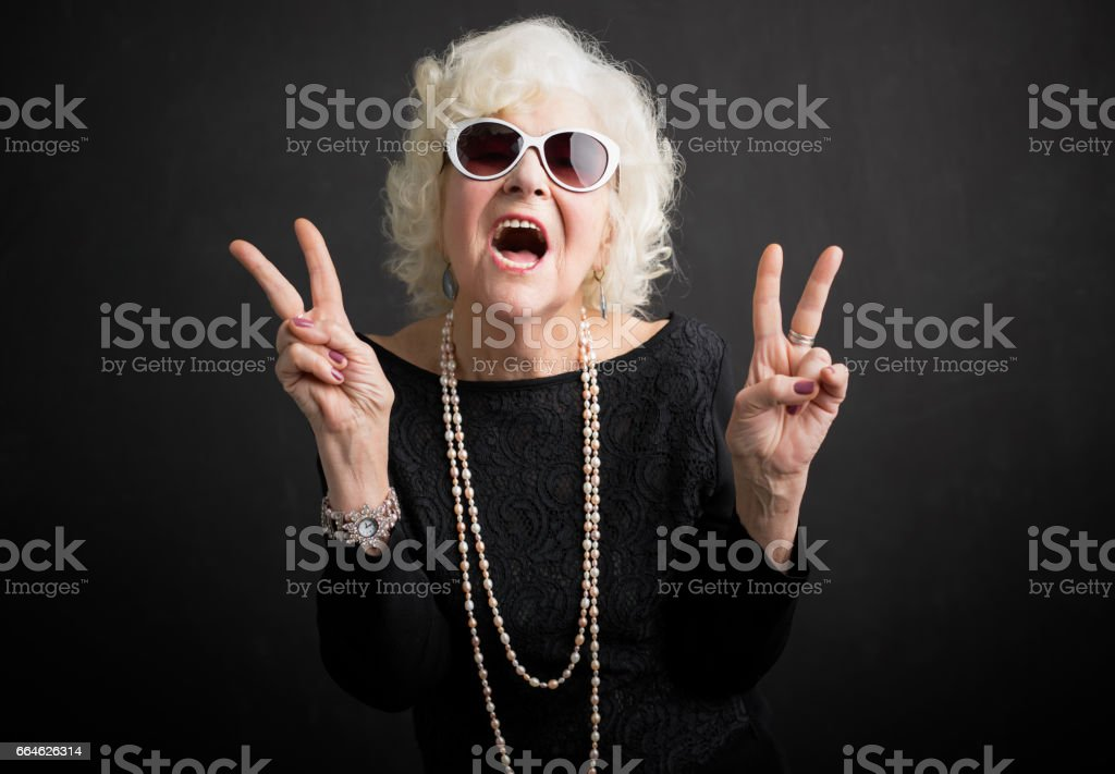 Cool grandmother showing peace sign stock photo