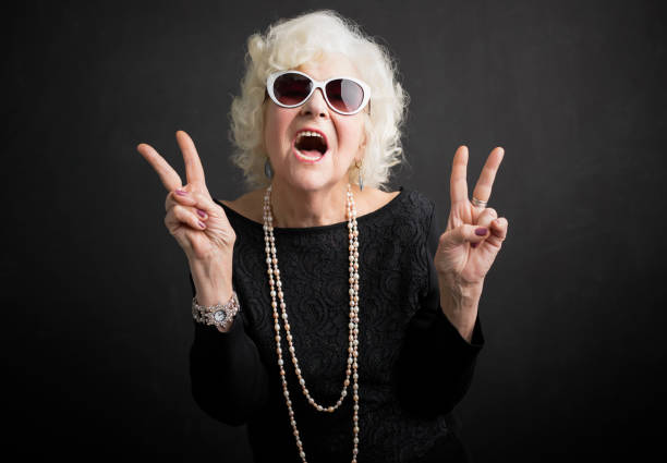 cool grandmother showing peace sign - enjoying wealthy life imagens e fotografias de stock