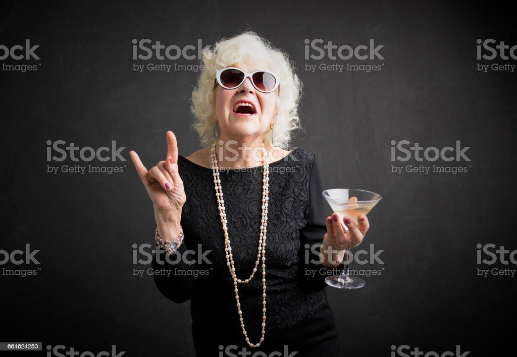 Arrefecer a avó com óculos de sol e beber na mão foto de stock royalty-free