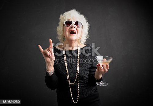 istock Cool grandmother with sunglasses and drink in hand 664624250