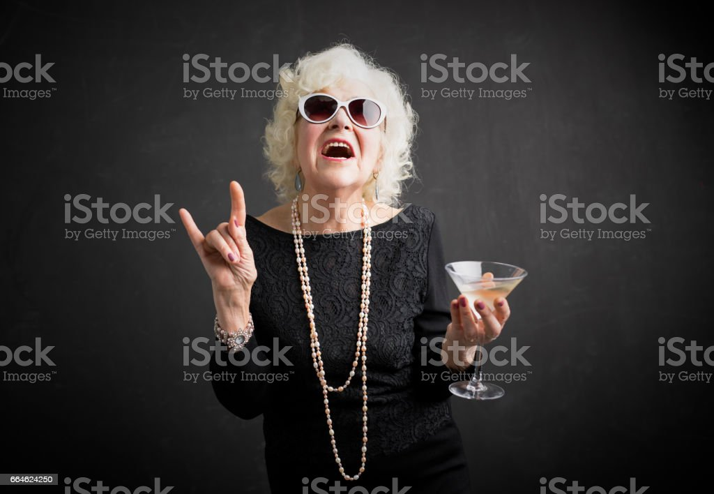 Cool grandmother with sunglasses and drink in hand stock photo