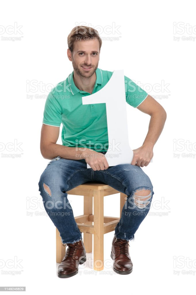 cool guy holds number one sign while sitting stock photo