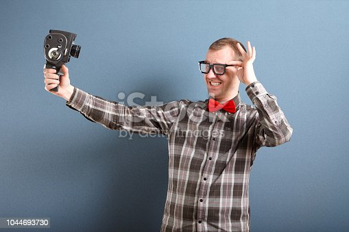 Nerdy man making funny face and holding old camera