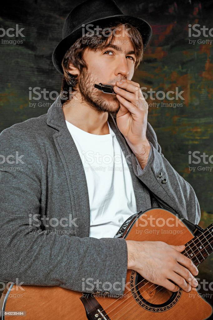 Cool guy with hat playing guitar on gray background stock photo