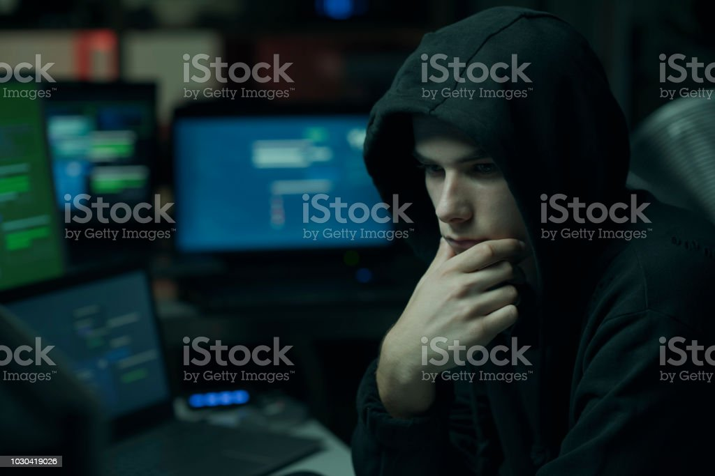 Cool hacker with hoodie working with computers stock photo