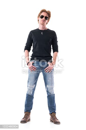 Cool handsome confident young man with sunglasses posing with thumbs in pockets. Full body isolated on white background.