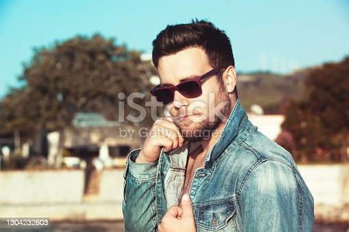 istock Cool handsome young man wearing jeans jacket and sunglasses 1304232603