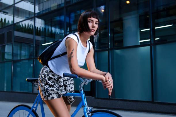 cooles hipster-mädchen posiert auf ihrem modernen blauen fahrrad - kurze schwarze haare stock-fotos und bilder