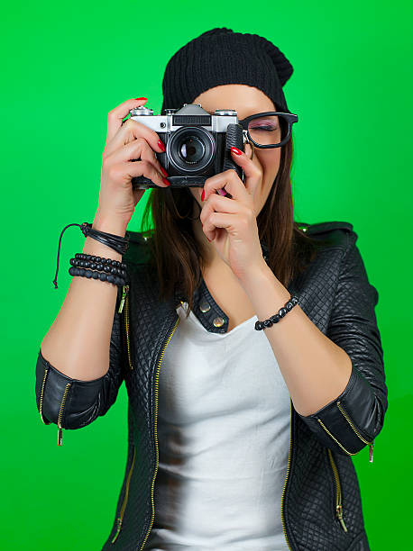 cool hipster girl taking a picture with old vintage camera - green screen background stock photos and pictures