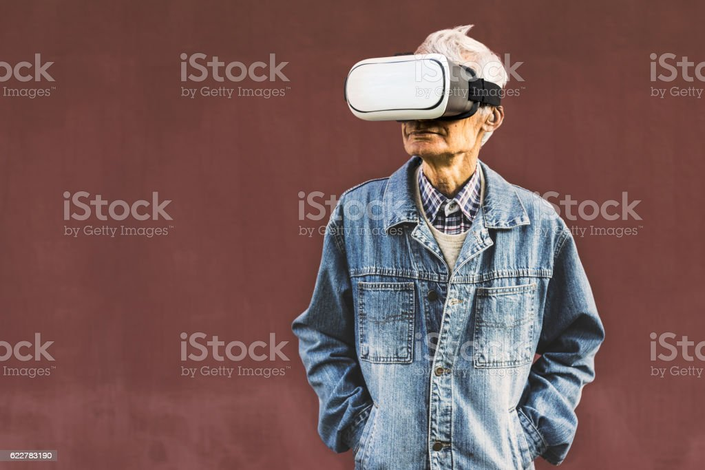 Cool hipster grandpa wearing virtual reality glasses stock photo
