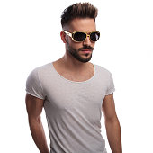 cool hipster in vintage rock and roll runglasses standing on white background