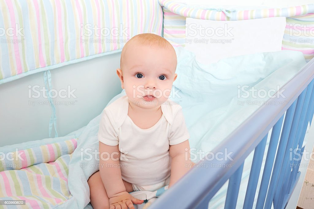 Cool kid sitting  baby bed  looks stock photo