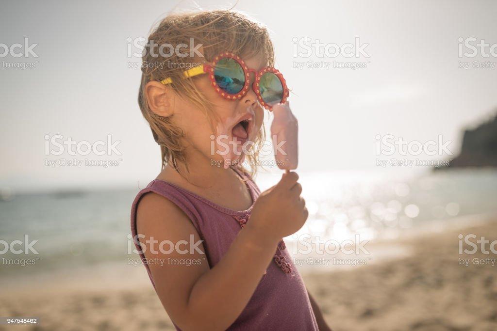 Cooles kleines Mädchen mit Eis im Sommerurlaub – Foto